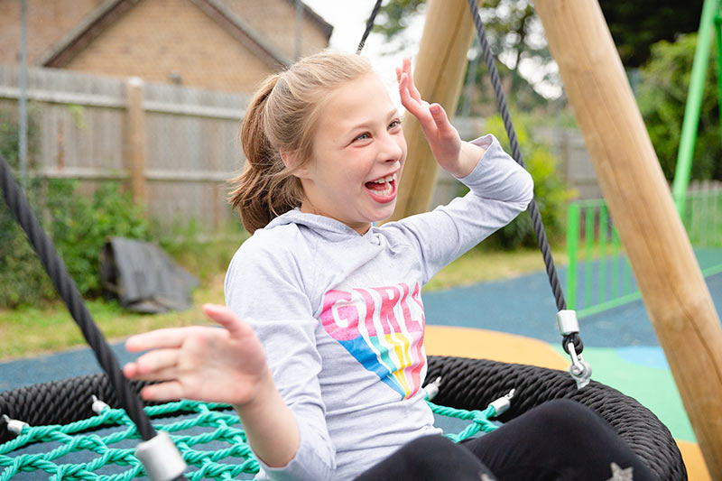 child enjoying herself on a swing donnington new homes